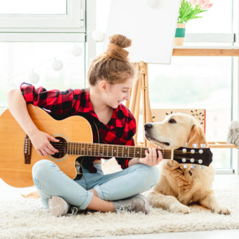 Girl playing guitar with lovely dog